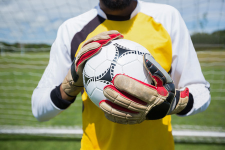 Mid section of goalkeeper with ball standing in front of goal post Banco de Imagens - 89774354