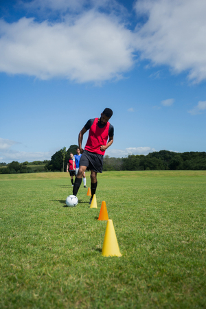 Soccer player dribbling through cones in the ground on a sunny day