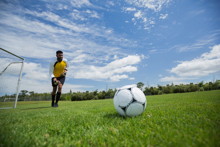 Goalkeeper ready to kick the soccer ball in the ground Stock Photo