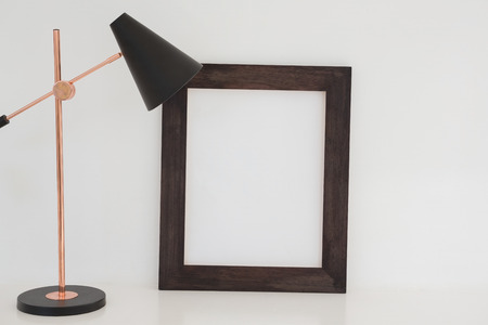 Table lamp and blank picture frame on table against white wall