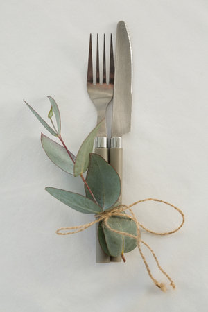 Close-up of fork and butter knife tied with leaf