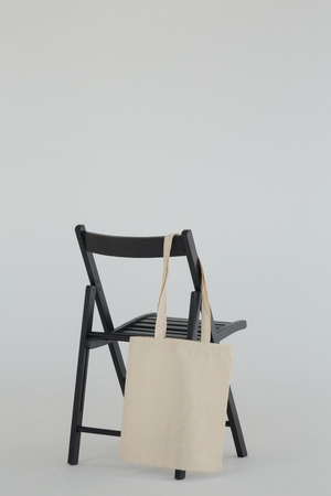 Close-up of grocery bag hanging on black chair Banque d'images