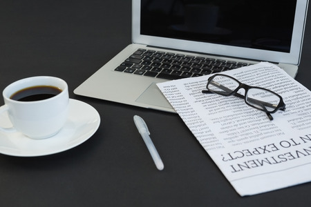 Close-up of coffee cup, laptop, spectacles, newspaper and pen on black background