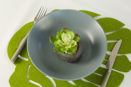 Overhead view of flower in bowl with fork and butter knife on a table cloth Stock fotó