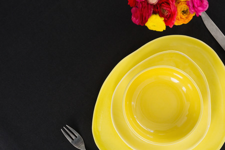 Close-up of table setting with yellow bowl and plates