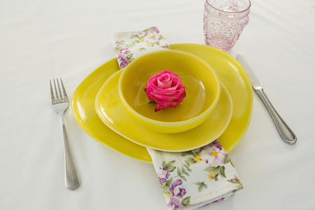 Close-up of rose flower in a bowl with cutlery Stock Photo