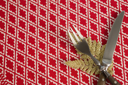 Close-up of christmas ornament with fork and butter knife on table cloth