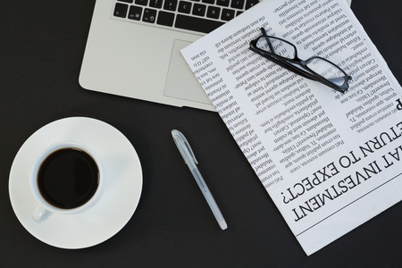 Overhead of cup of coffee, laptop, spectacles, newspaper and pen on black background