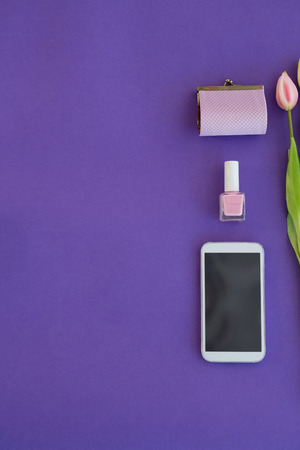 Overhead of tulips, purse, nail polish and mobile phone arranged on purple background Banque d'images