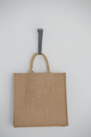 consumerism: Close-up of jute hanging on hook against white wall Stock Photo