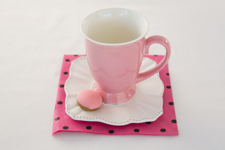 Close-up of pink mug with macaron on a dish Banque d'images