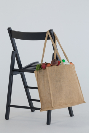 Close-up of fresh vegetables bag hanging on black chair