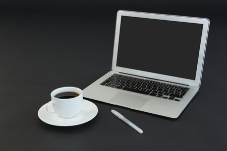 Close-up of coffee cup, laptop and pen on black background