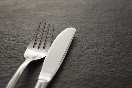 Close-up of fork and knife on black background