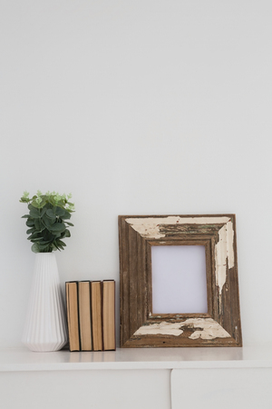 Close-up of wooden frame, vase and books arranged on table