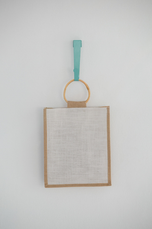 Close-up of bag hanging on hook against white wall Banque d'images