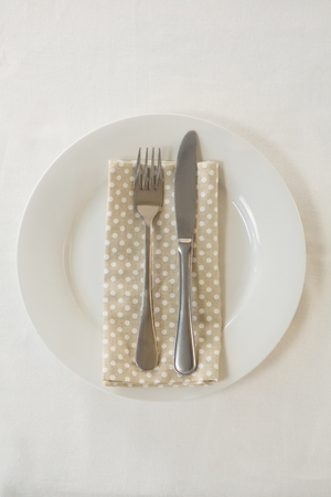 Close-up of fork and butter knife with napkin arranged in a plate