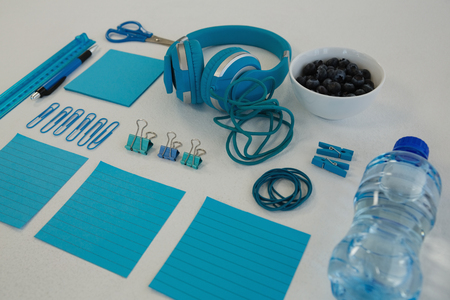 Close-up of headphones, blueberries, water bottle and stationery on white background