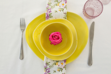 Overhead view of rose flower in a bowl with cutlery
