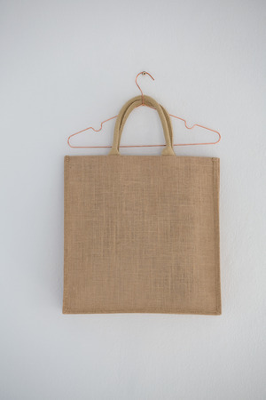 Close- up of jute bag hanging on wall with hanger