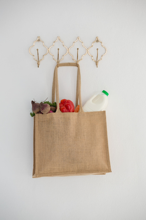 Fresh vegetables and bottle in bag hanging on hook