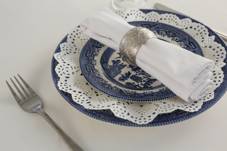 Close-up of fork, napkin and lace placemat arranged on white background Banque d'images