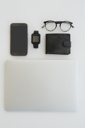 Overhead of various gadgets, spectacles and wallet on white background