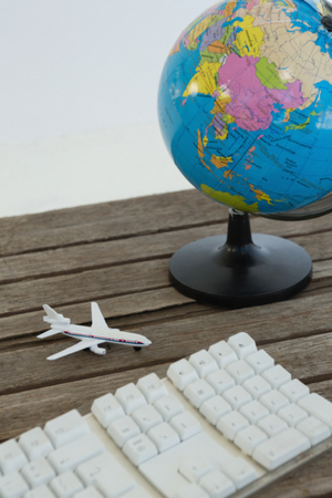 Close-up of globe, airplane model and keyboard on wooden plank Banque d'images