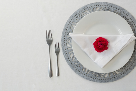 Overhead view of elegant table setting with doily paper