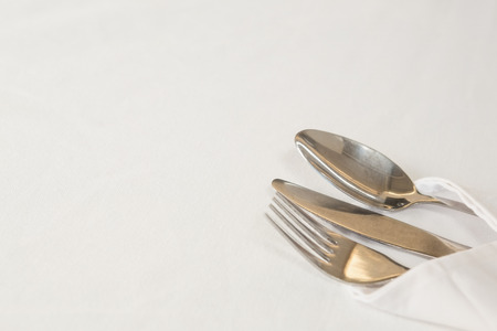 Fork, butter knife and spoon in napkin on white background