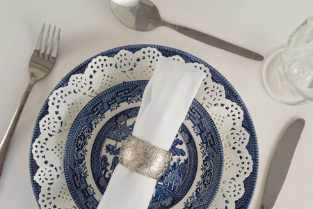 Fork, butter knife, spoon, napkin and lace placemat arranged on white background Banque d'images
