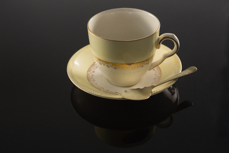 Close-up of empty cup with saucer and spoon on black background Stock Photo