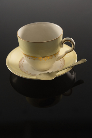 Close-up of empty cup with saucer and spoon on black background Banque d'images
