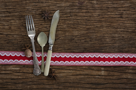 Cutlery with star anise and nutmeg on wooden table