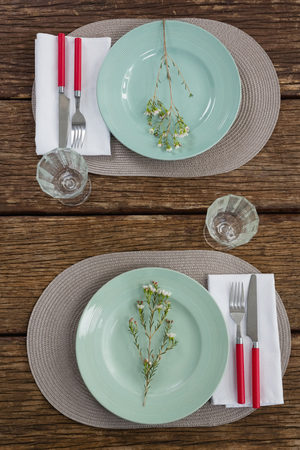Overhead view of fork and butter knife with napkin and flower on plate Archivio Fotografico