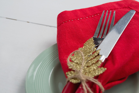 Close-up of fork and butter knife with napkin and christmas ornament tied up with a rope Stock Photo