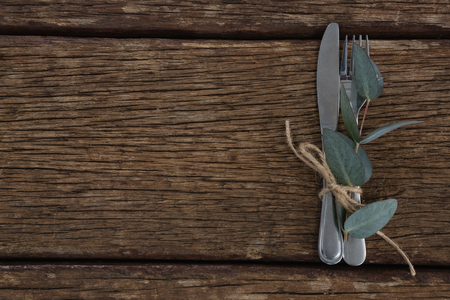 Overhead view of fork, butter knife tied up with leaf on wooden table Stock Photo