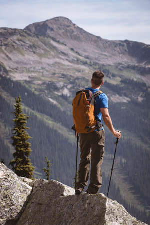 Male hiker looking at solar eclipse on a rocky mountain LANG_EVOIMAGES