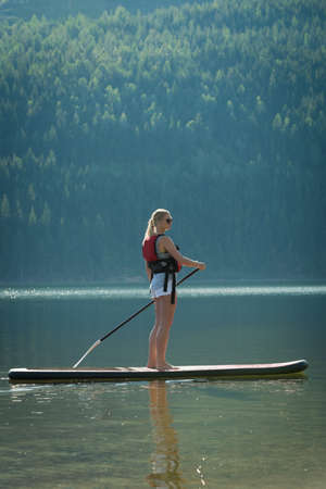 Woman doing stand up paddleboarding in river on a sunny day