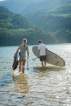Couple with stand up paddleboard walking in river on a sunny day