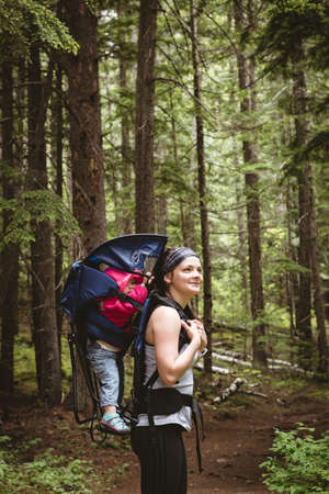 Mother carrying her baby in backpack carrier in forest LANG_EVOIMAGES