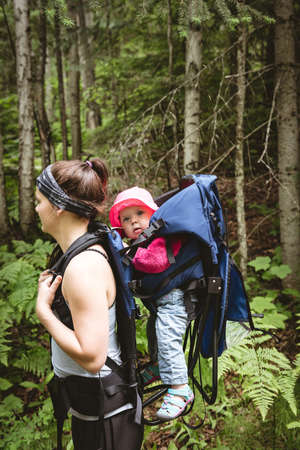 Mother carrying her baby in backpack carrier while hiking