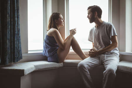 Couple having cup of coffee near window at home