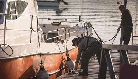 Fishermen tying buoy on boat at harbor