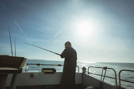 Fisherman fishing with fishing rod from the boat LANG_EVOIMAGES