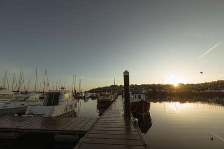 Moored boat and empty jetty at harbor during sunset