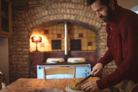Man cutting bun with knife at home