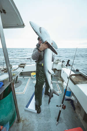 Fisherman holding shark fish in boat