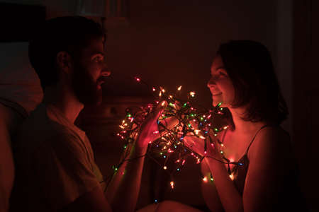 Romantic couple holding fairy lights in dark room at home