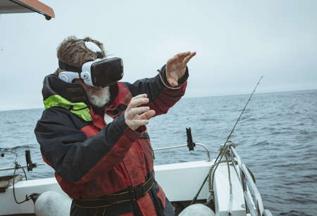 Fisherman using virtual reality headset on boat LANG_EVOIMAGES